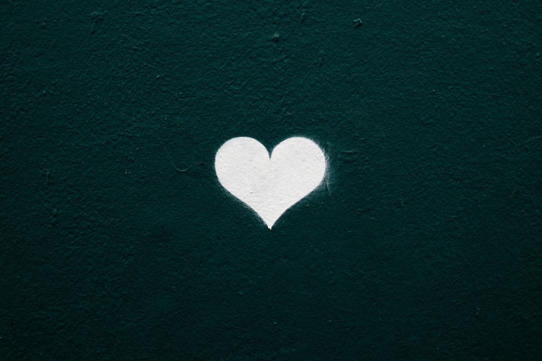 A white heart drawn on a dark green background