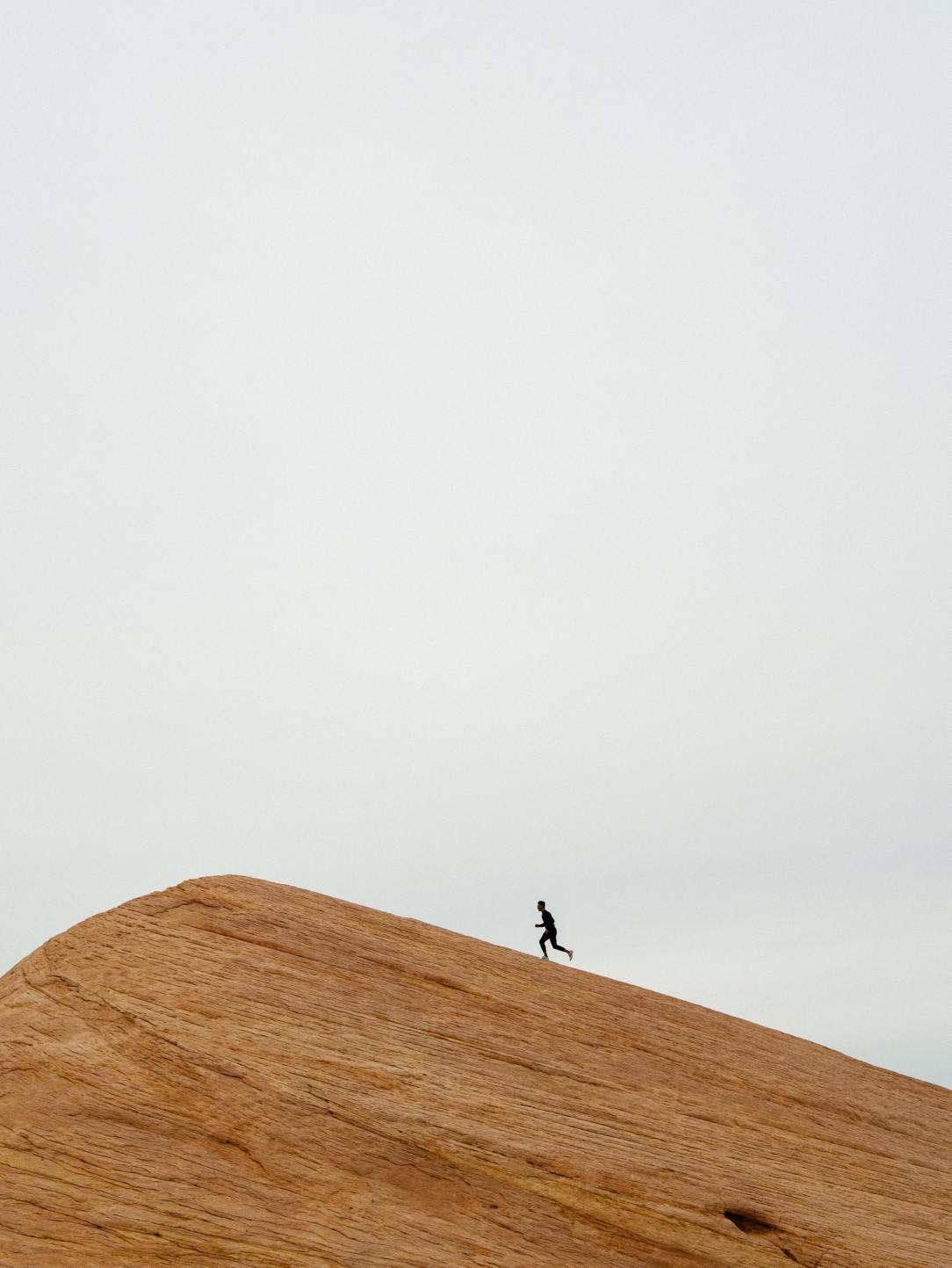 A person running on a desert hill