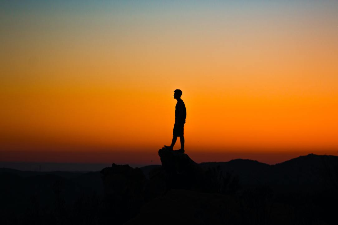 A person standing on a giant rock in the sunset.